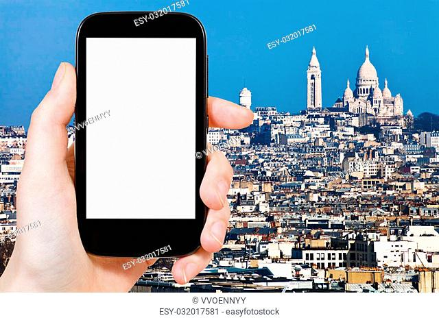 travel concept - hand holds smartphone with cut out screen and Montmartre Hill in Paris on background