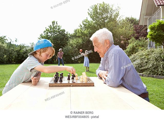 Grandfather and grandson playing chess in garden