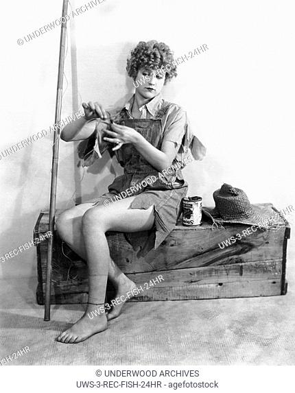 California: c. 1925 A young woman ready to go fishing attempting to bait her hook