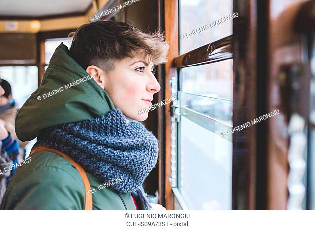 Young woman looking out of cable car window
