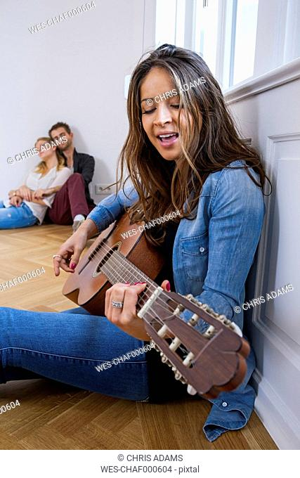Young woman sitting on floor playing guitar with couple in background