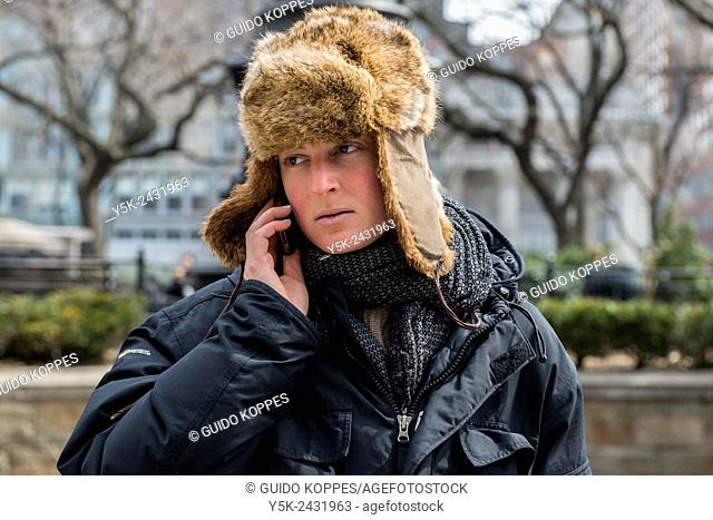 New York, USA. Young, caucasian woman, wearing a bond cap, while making a mobile phone call in Union Square Park, Manhattan
