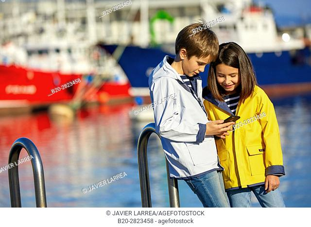 Children with raincoat, Port of Getaria, Gipuzkoa, Basque Country, Spain, Europe