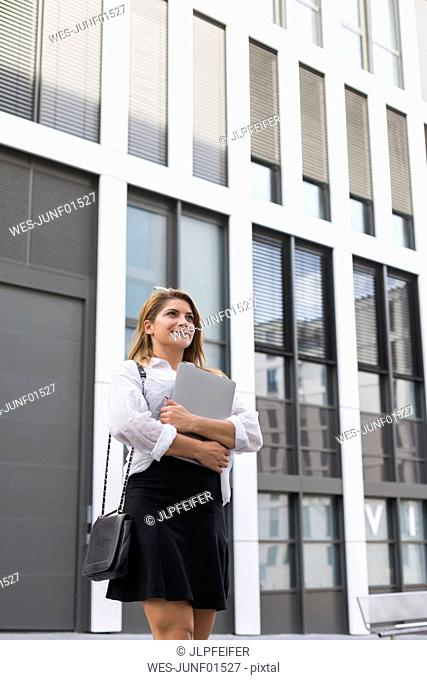 Portrait of smiling businesswoman with laptop outdoors