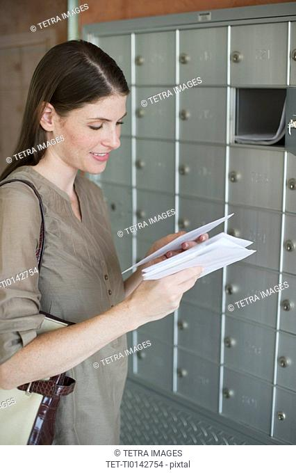 Woman checking post next to mailboxes