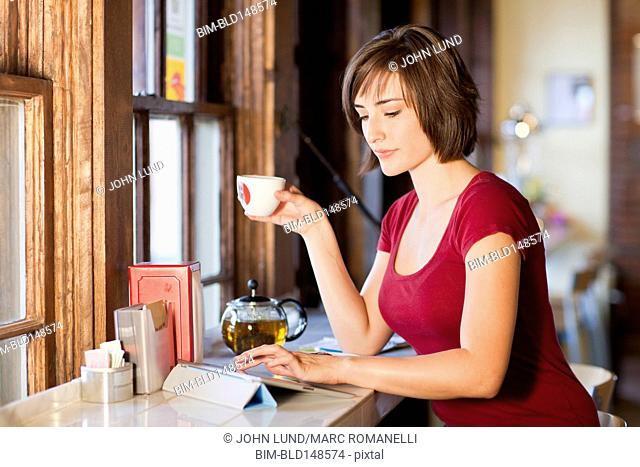 Hispanic woman using digital tablet in cafe