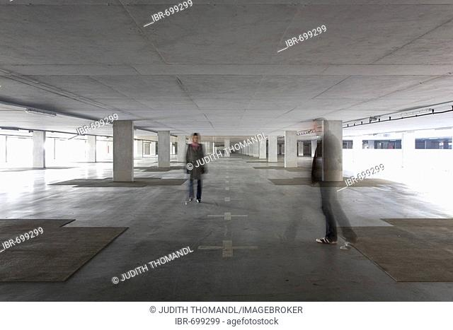 Two people in a deserted parking garage