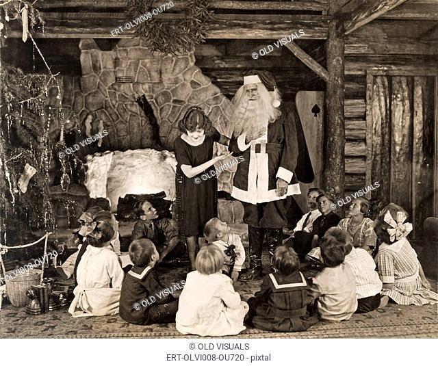 Woman introducing Santa Claus to children during Christmas