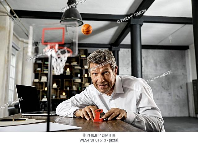 Portrait of mature business man playing office games in loft