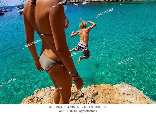 Young boy jumping into sea. Cala Salada beach. Santa Agnés de Corona. Ibiza. Balearic Islands. Spain