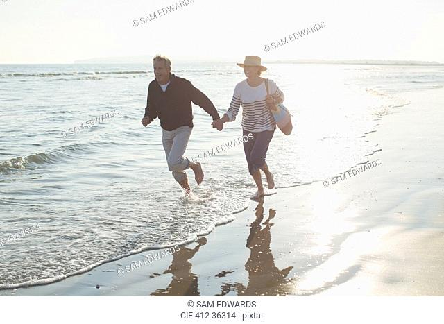 Playful mature couple holding hands and running in sunny ocean surf