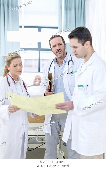 Three doctors with report in a hospital room