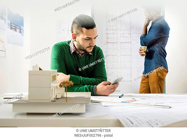 Two young architects in office with cell phone and construction plan