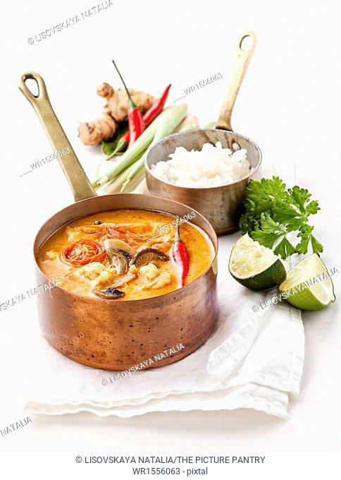 Spicy Thai soup Tom Yam with Rice, Chili pepper and Seafood on white background