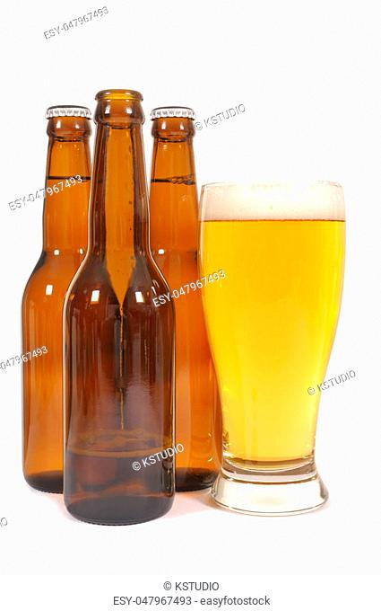 Glass of beer with brown bottles one half empty