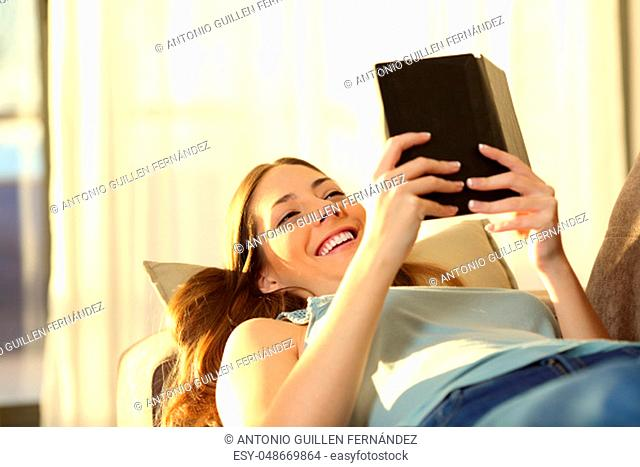 Woman reading an e book lying on a couch in the living room at home with a window and a warm light in the background