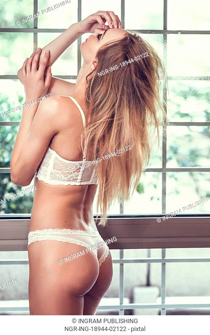 Beautiful blonde woman in white lingerie posing near a window. Young girl wearing underwear with long hair