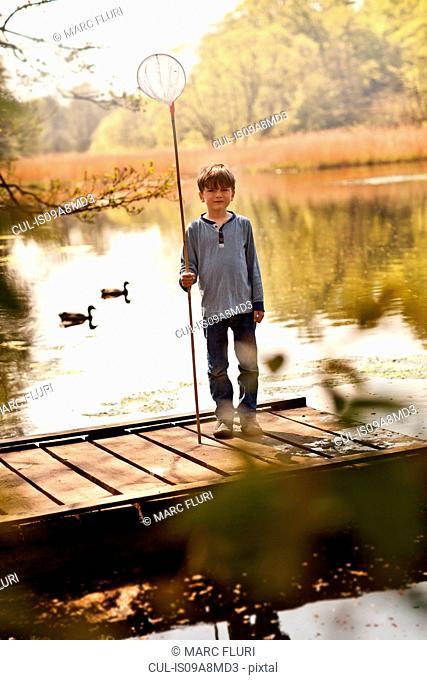 Boy standing on pier holding fishing nets, portrait