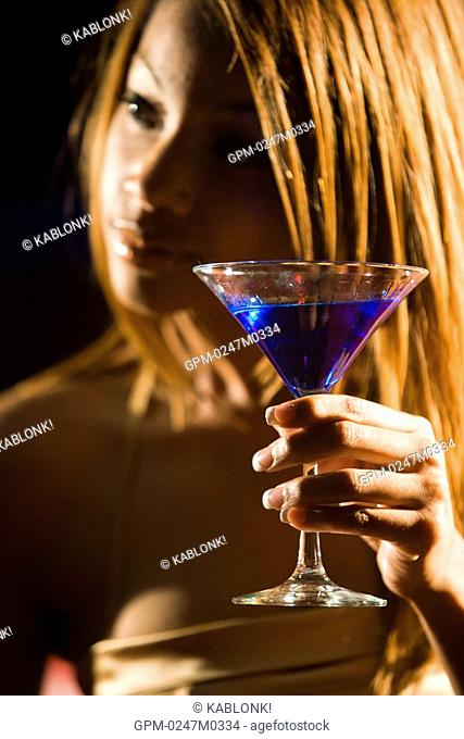 Close-up of young African American woman holding martini glass at nightclub