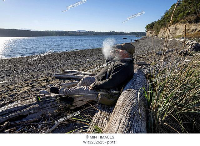 A fly fisherman enjoys a cigar and takes a break from fly fishing for searun coastal cutthroat trout and salmon in northwest Washington State USA