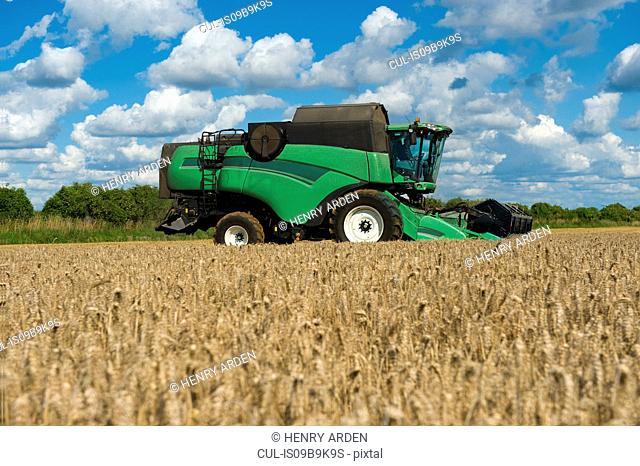Combine harvester harvesting rural field