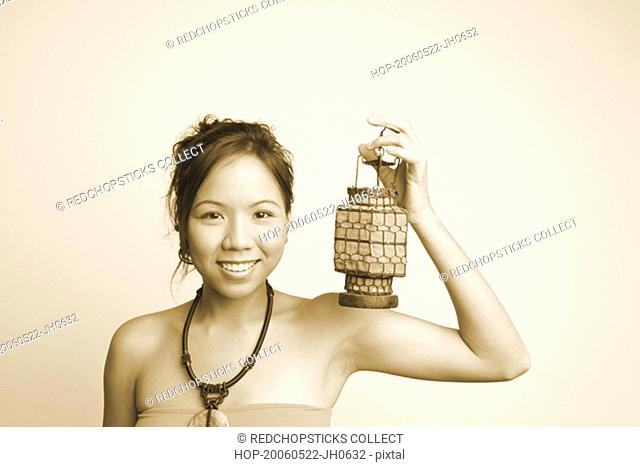 Portrait of a young woman holding a lantern and smiling