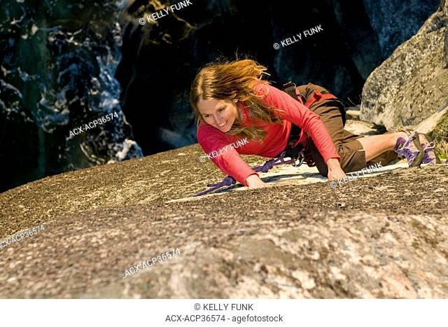 A female rock climber ascends a route at Stillwater bluffs near Powell river on the upper Sunshine coast, Vacouver coast and mountain range, British Columbia