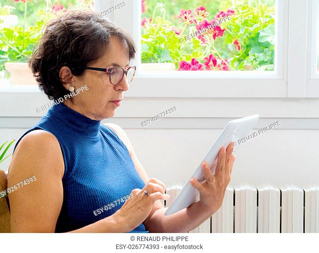 a portrait of a mature woman with a tablet