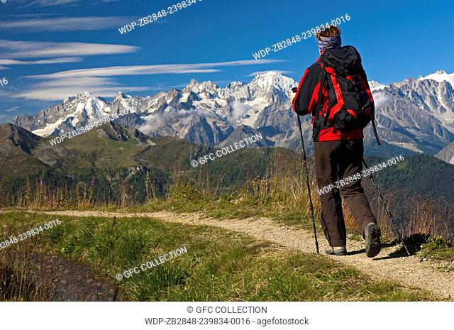 Hiker on a hike along the historic Verbier irrigation canal, Bisse de Verbier, in front of the ice and snow covered peaks of the Valais Alps, Valais