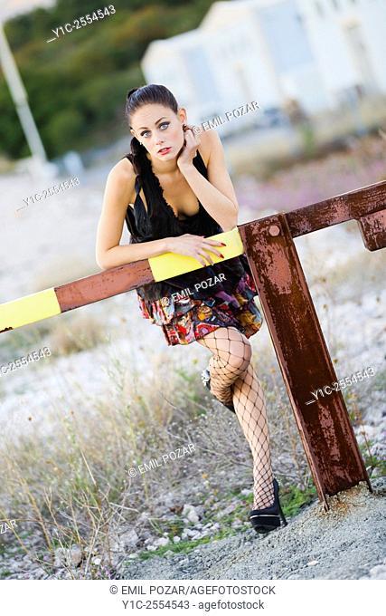 Pretty teen girl bent over a rusty ramp