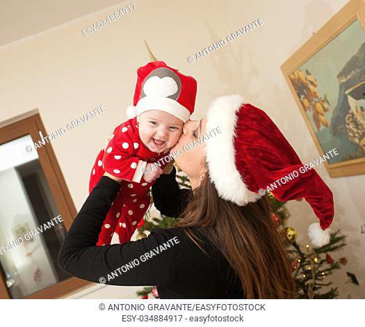 Newborn baby girl with Christmas suit playing with her mom