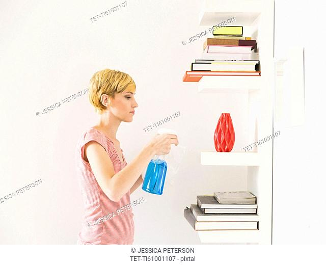 Young woman cleaning bookshelf