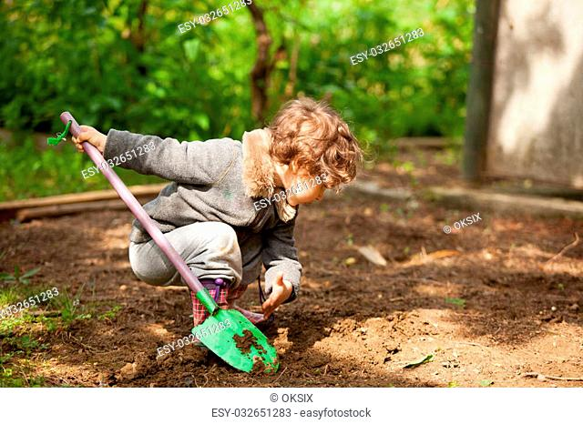 Little girl in rubber boots holding a shovel and tried to dig