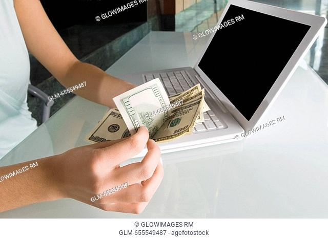 Mid section view of a businesswoman counting paper currency in front of a laptop