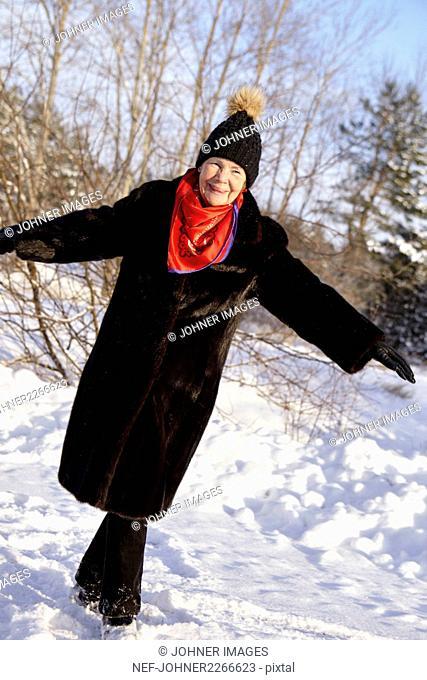 Senior woman walking in forest in winter