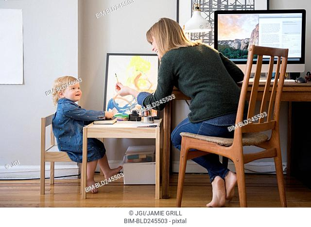 Caucasian mother working and daughter playing in home office