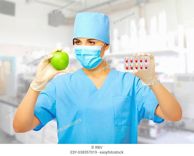 Young doctor with green apple and pills isolated