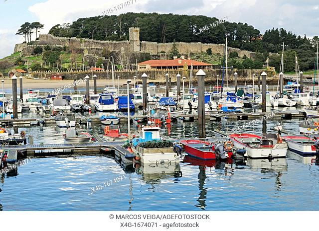 Traditional fishing boats in Baiona and Monte Real Castle on the background  Galicia, Spain
