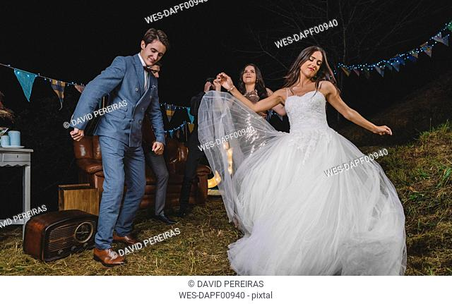 Happy bride dancing and having fun with her friends on a night field party