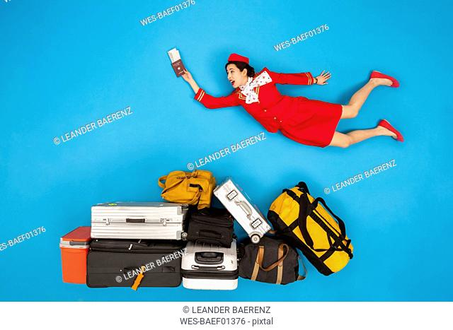 Flight attendant holding passport and tickets, flying over luggage