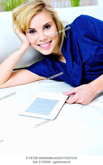 young, pretty woman reading e-book