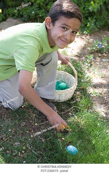 Young boy reaching for Easter egg hidden in grass