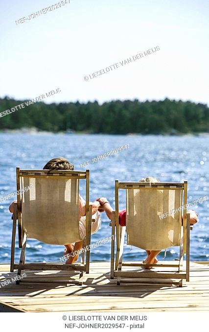 Couple on deckchairs at lake