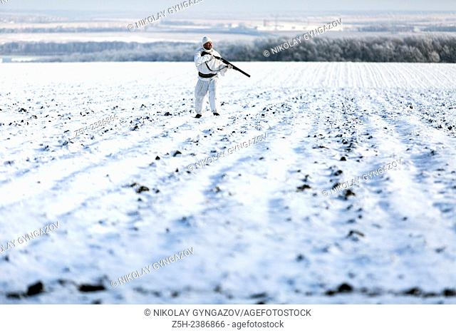 Russian Federation. Voronezh oblvst. Hunter in camouflage white suit on winter hunting