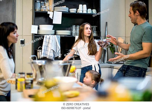 Husband and wife talking to daughter in kitchen, toddler girl reaching for lemons