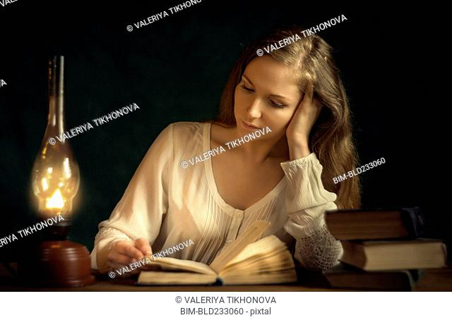 Caucasian woman reading book by candlelight