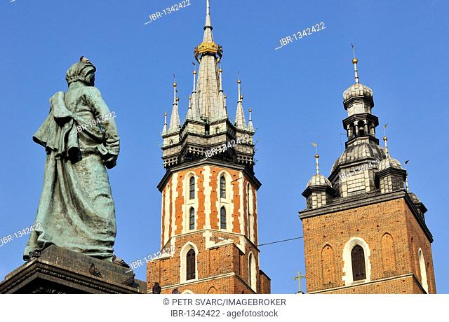 Detail of towers of St. Mary's Basilica, Kosciol Mariacki, and Adam Mickiewicz Monument in Main Market Square, Rynek Glowny, in Krakow, Cracow, Poland, Europe