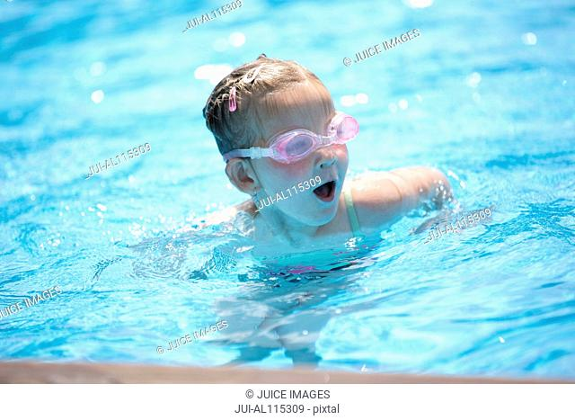 Young girl in swimming goggles in pool