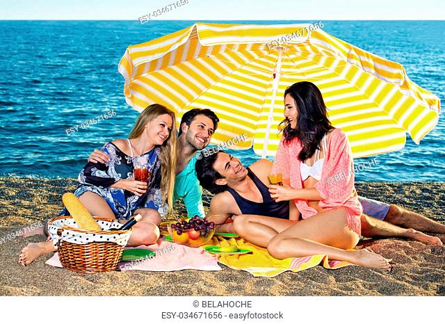 Smiling attractive friends share grapes apples and oranges seated next to wicker basket with bread and wine on the beach