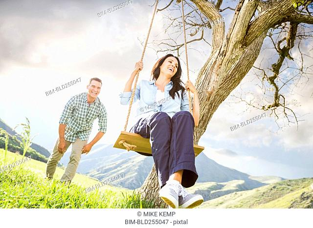 Man pushing woman swinging on tree swing